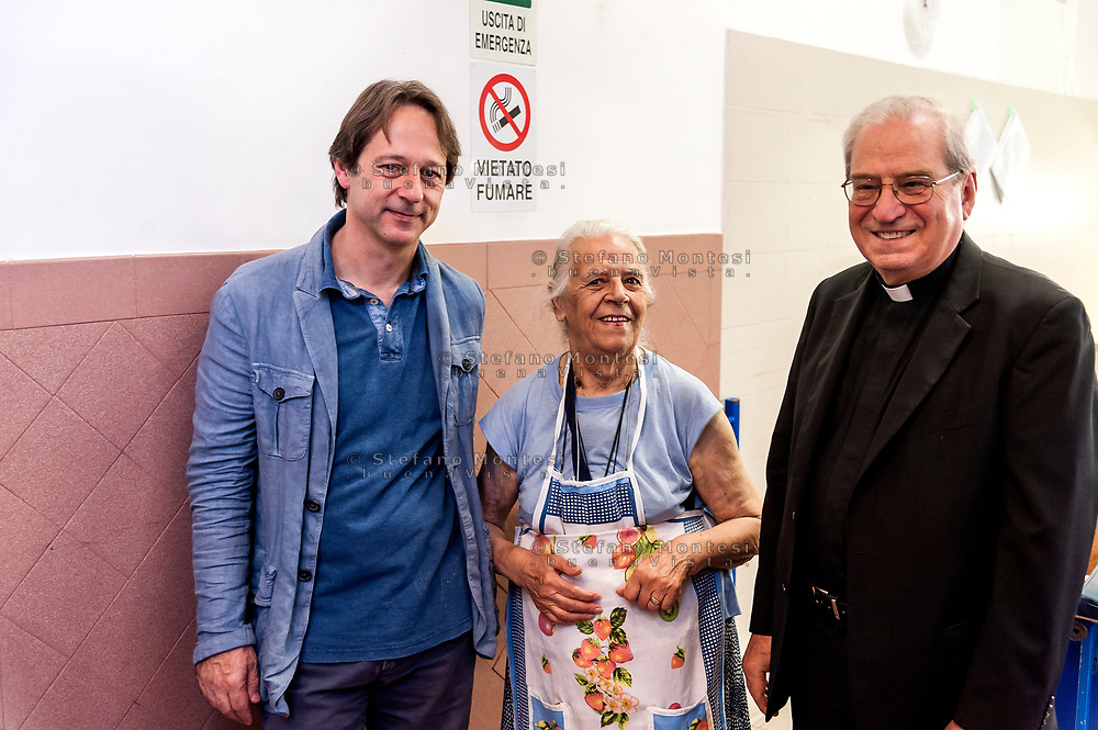 ROME, ITALY - AUGUST 15: The director of Caritas Rome, Msgr. Enrico Feroci and the Deputy Mayor Luca Bergamo with a volunteer during visits the Caritas canteen of Colle Oppio on the mid-August holiday on August 15, 2017 in Rome, Italy. Caritas canteen of Colle Oppio  provide about 500 meals a day for lunch.