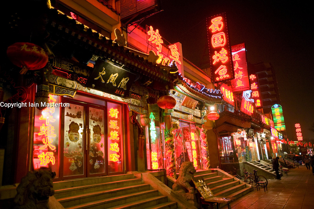 "Bright neon lights and red lanterns at night outside traditional restaurants on ""Ghost Street"" in central Beijing, a historic street famed for its many restaurants February 2009"
