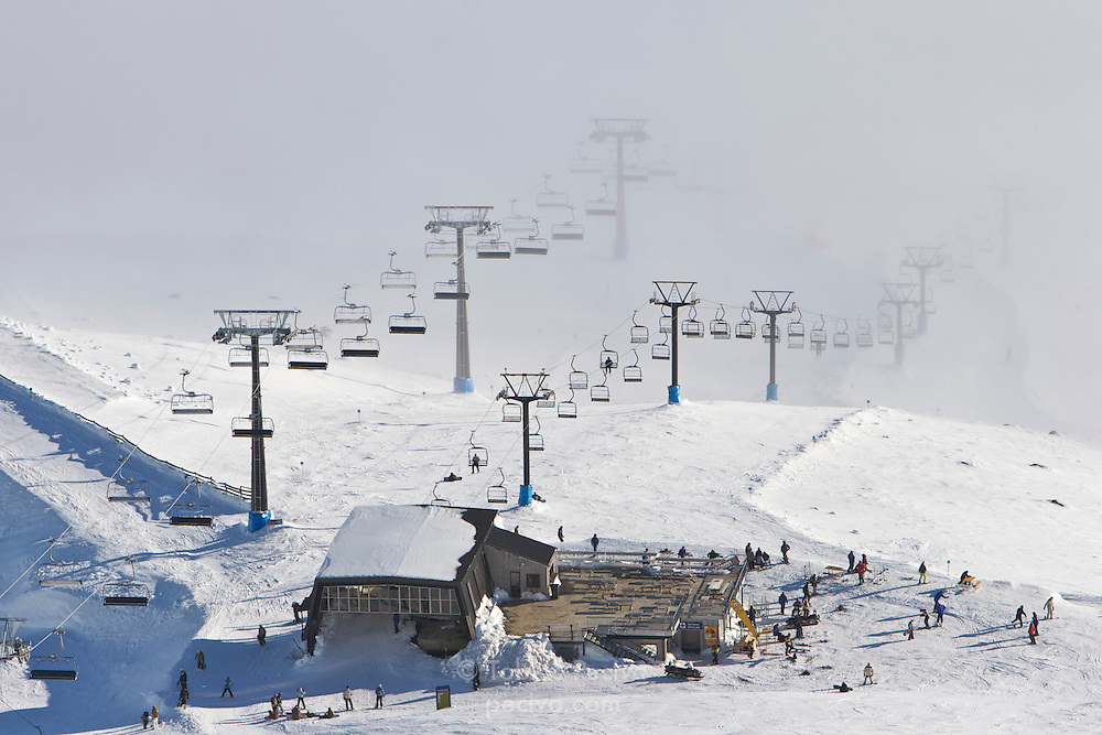 Two chairlifts emerge from low cloud cover at ski field Turoa. Turoa is located on active volcano Mount Ruapehu, New Zealand.