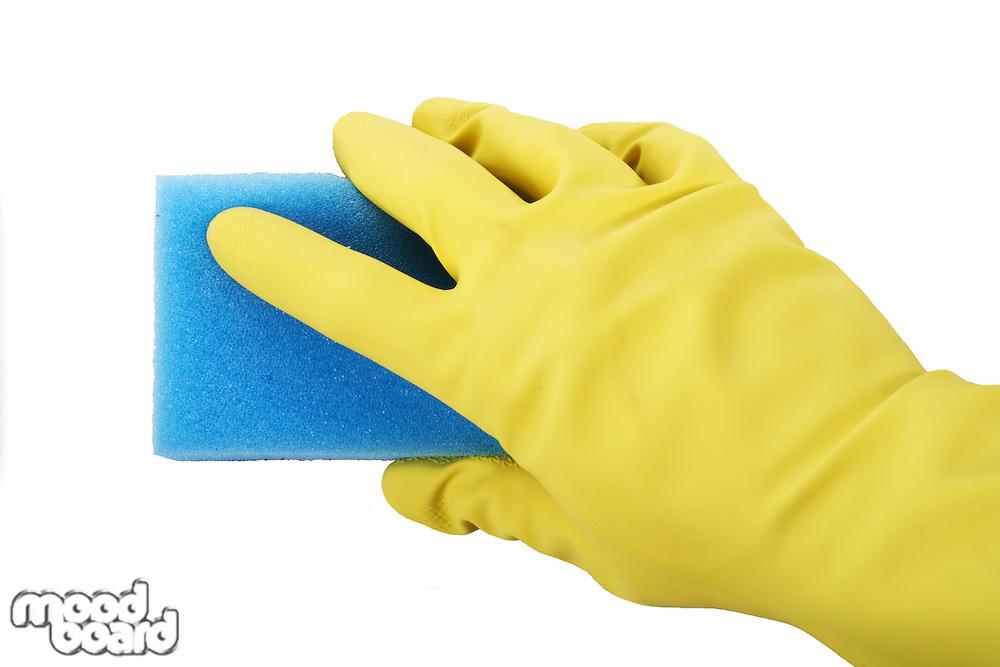 Hand in rubber gloves holding sponge