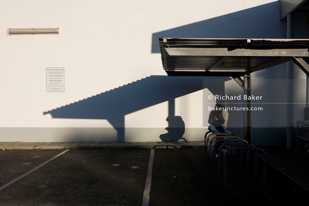 A lone man makes a smartphone call beneath a supermarket shelter with its long shadows across three parking bays.