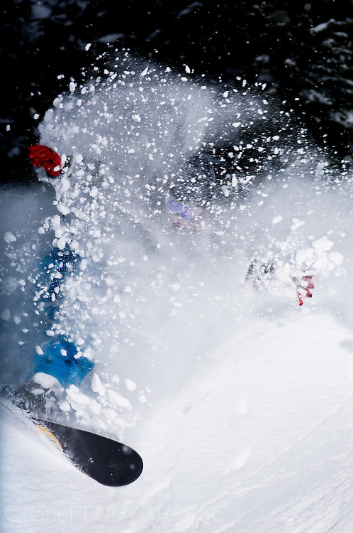 professional snowboarder shin campos gets lost in the spray of his own turn on a stormy day on whistler mountain, british columbia, canada