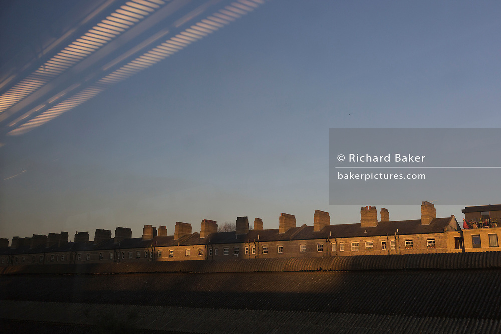 Seen from the window seat of a train carriage that is travelling into Victoria station, is a landscape of Pimlico housing, in London, England, on 4th December 2019.