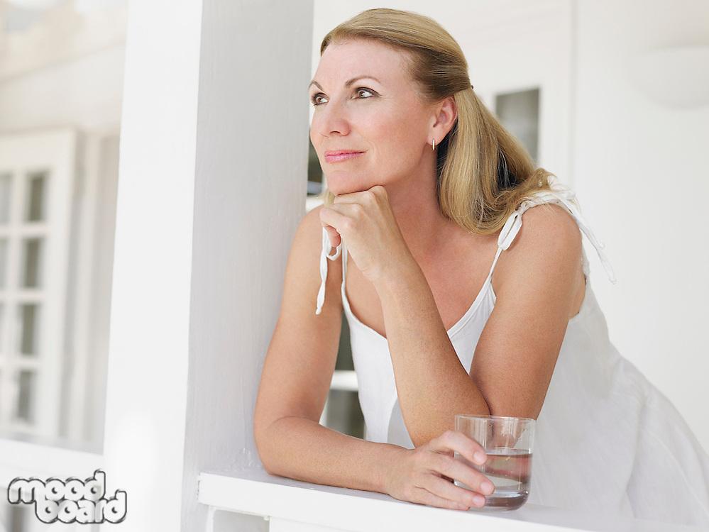 Woman holding glass of water leaning on verandah balustrade portrait