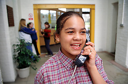 Teenage girl using pay phone in youth club; smiling,