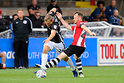 Harry Anderson (26) of Lincoln City is tackled by Jake Taylor (25) of Exeter City during the EFL Sky Bet League 2 match between Exeter City and Lincoln City at St James' Park, Exeter, England on 19 August 2017. Photo by Graham Hunt.