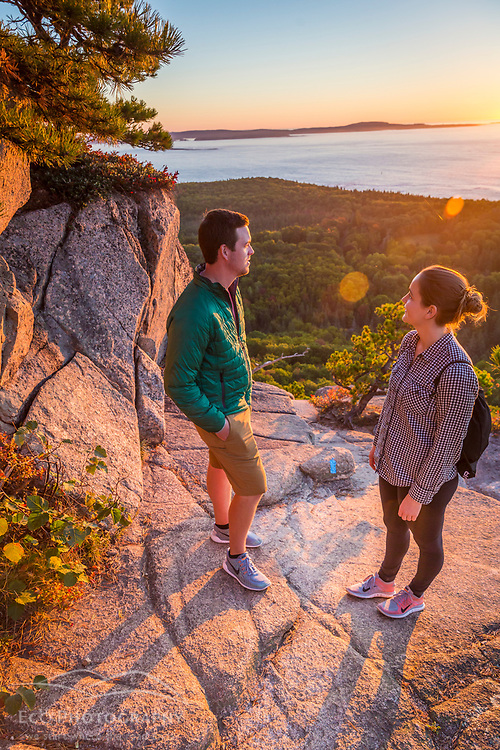 """A young couple watches the sunrise from a ledge on """"The Beehive"""" in fall in Maine's Acadia National Park."""