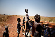 Children wait for water to be delivered in old oil cans next to an exploratory oil rig in Upper Nile State.