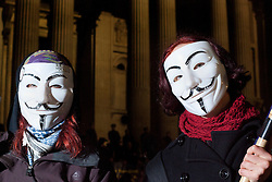 © Licensed to London News Pictures. 28/02/2012. LONDON, UK. Two protesters wearing Guy Fawkes masks stand outside a cordon as police and bailiffs remove the Occupy London campsite in London today (28/02/21). After being camped outside St Paul's Cathedral in London for four months anti-capitalist Occupy London demonstrators were tonight evicted by police and bailiffs who moved in shortly after midnight. Photo credit: Matt Cetti-Roberts/LNP