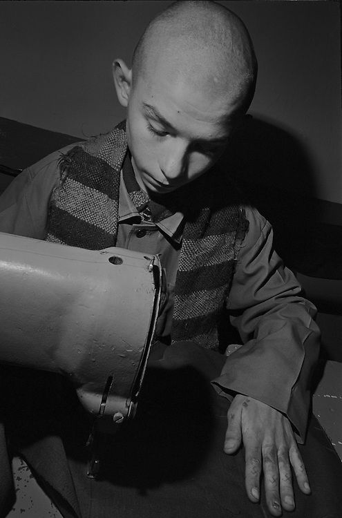 A prisoner boy sews on a machine the overalls for prisoners at the colony for prisoner's children in Siberian town Leninsk-Kuznetsky, Russia, 26 January 2000.