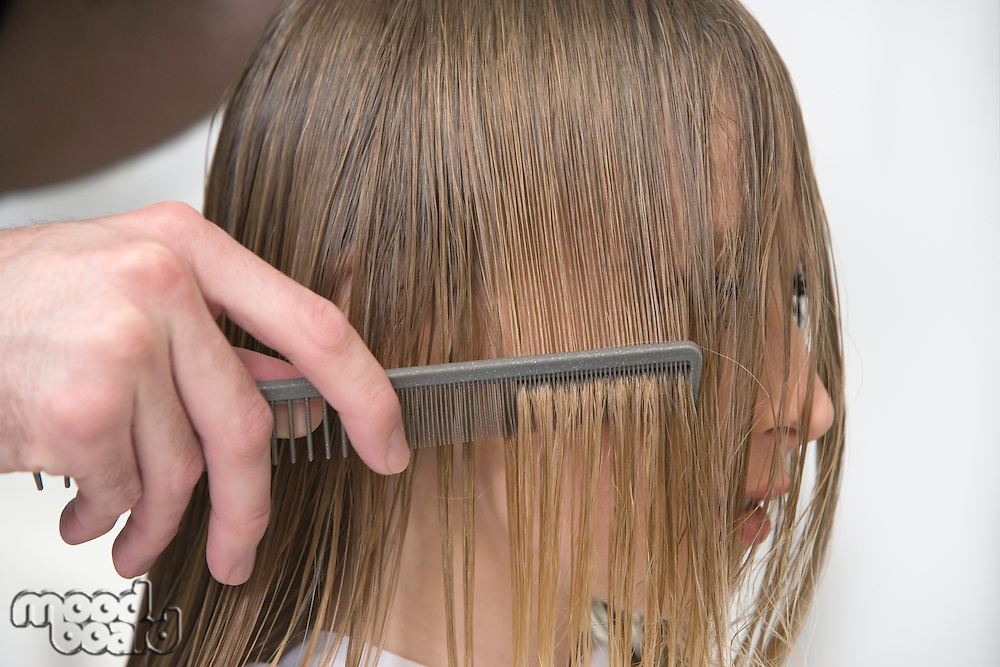 Combing a womans wet hair in the hairdressers
