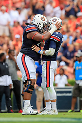 Auburn Tigers offensive lineman Wilson Bell (74) and quarterback Jarrett Stidham (8) celebrate during an NCAA football game against the Mississippi Rebels, Saturday, October 7, 2017, in Auburn, AL. Auburn won 44-23. (Paul Abell via Abell Images for Chick-fil-A Peach Bowl)
