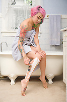 Woman in towel shaving her leg on side of the bathtub
