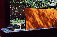 Catching some sun rays next to a work of art in a small park on 2nd Avenue at 80th street in New York City