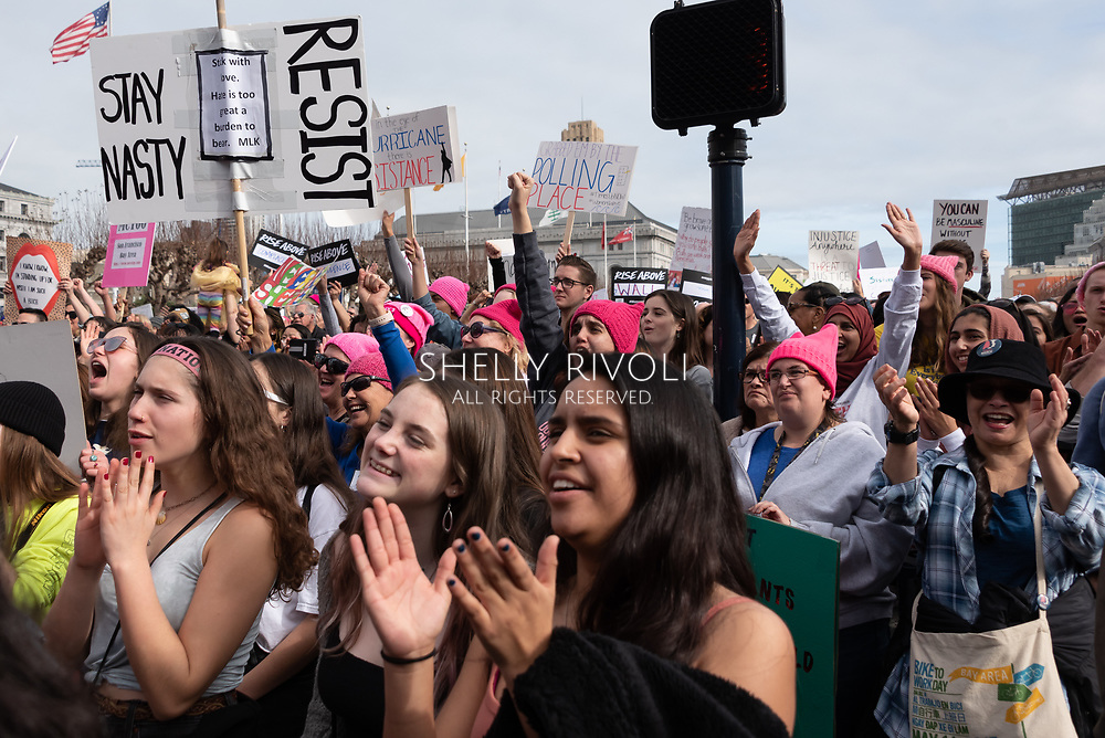 San Francisco, USA. 19th January, 2019. The Women's March San Francisco begins with a rally at Civic Center Plaza in front of City Hall. Young women clap near the front of a cheering crowd during the rally. Credit: Shelly Rivoli/Alamy Live News