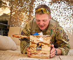 © licensed to London News Pictures. AFGHANISTAN  25/06/1. Sergeant Mick Welsh, 39 from Jarrow, Tyne on Wear opens one of many Afghan Heroes gift boxes that have been sent out to troops in Afghanistan to mark Armed Forces Day in Helmand today (25 Jun 11).. Please see special instructions. Photo credit should read Alison Baskerville/LNP