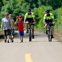THOMAS WELLS | BUY at PHOTOS.DJOURNAL.COM<br /> Ariel McGregor, from left, Shane McGregor, 12, and Xavier McGregor, 11, walk along the tanglefoot trail with Pontotoc Bicycle officers Nathan Gregory and Brad Owen while on patrol this week.
