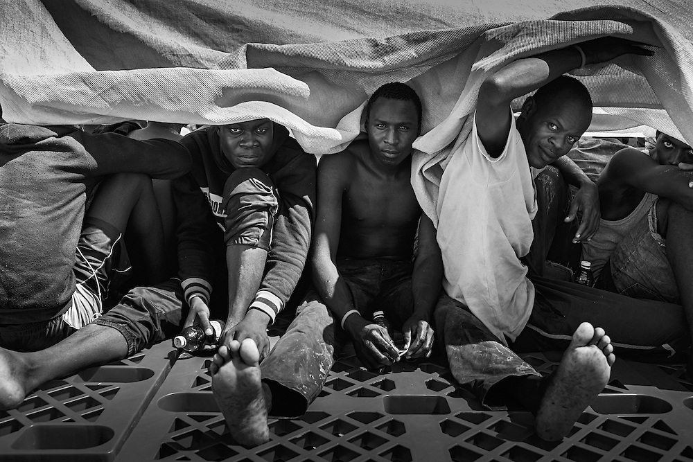 International waters off the Libyan coast. Aboard MOAS Responder. Part of 314 rescued people are chatting and resting on desk, on the way back to Italy. After the rescues, all the people are accommodated on the boat deck, checked on by medical staff, rehydrated and fed on energy bars. Usually the long trip back to Italy begins, but sometimes the Central Operative Italian Coastguard in Rome may require to transfer all the people to another bigger and faster ship, and to stay in S.A.R. zone due to lack of other rescue ships in the area.