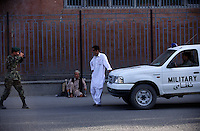 Kabul, 26 July 2005...Afghan soldier taking a picture of his friend next to the military car, wearing a white salwar chemise. ..The one-leg man is taking a break.