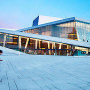 The Oslo Opera House (Operhuset) in Olso, Norway, at sunset. Designed by the Norwegian firm Sn&oslash;hetta, the building was completed in 2007 and is the home of the Norwegian National Opera and Ballet, and the national opera theatre in Norway. It is situated in the Bj&oslash;rvika neighborhood of central Oslo, at the head of the Oslofjord.<br />
