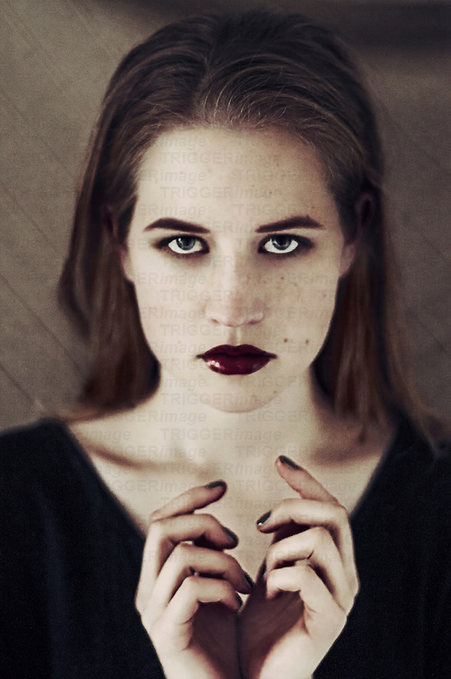 Dark portrait of young woman with dark make-up