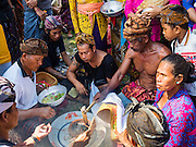 15 JULY 2016 - GIANYAR, UBUD, BALI, INDONESIA:  Family members of a deceased pray over a small flame taken from the cremation pyre during the community wide cremation in Gianyar. Most of the people on Bali are Hindus. Traditional cremations in Bali are very expensive, so communities usually hold one mass cremation approximately every five years. Most of the mass cremations in Bali are held in late June or early July. Gianyar, a small village about 30 minutes from Ubud, held their village wide cremation Friday. The community wide mass cremation in Ubud is Saturday.       PHOTO BY JACK KURTZ