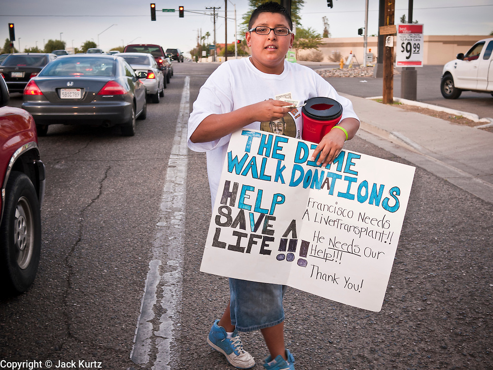 20 DECEMBER 2010 - PHOENIX, AZ: CARLOS OLIVAS stuffs money he's collected into a coffee can. He collects donations to help pay for a liver transplant for Francisco Felix from passing motorists on 75th Ave in Phoenix, AZ. Most of the donations come in the form of dimes. Felix is a patient in AHCCCS, Arizona's Medicaid agency. He needs a liver transplant and is one of the patients Arizona Governor Jan Brewer (R) kicked off the transplant list when she eliminated funding for transplants from AHCCCS. The move saved the state of Arizona about $1.4 million. Olivas read the AHCCCS cuts and started collecting dimes to help pay for transplants the state of Arizona won't pay for. He said he does it because he wants to set an example for other young people and because he hopes someone would do the same thing for his father if he needed a liver transplant. Carlos said that so far he's collected about $2500.   PHOTO BY JACK KURTZ