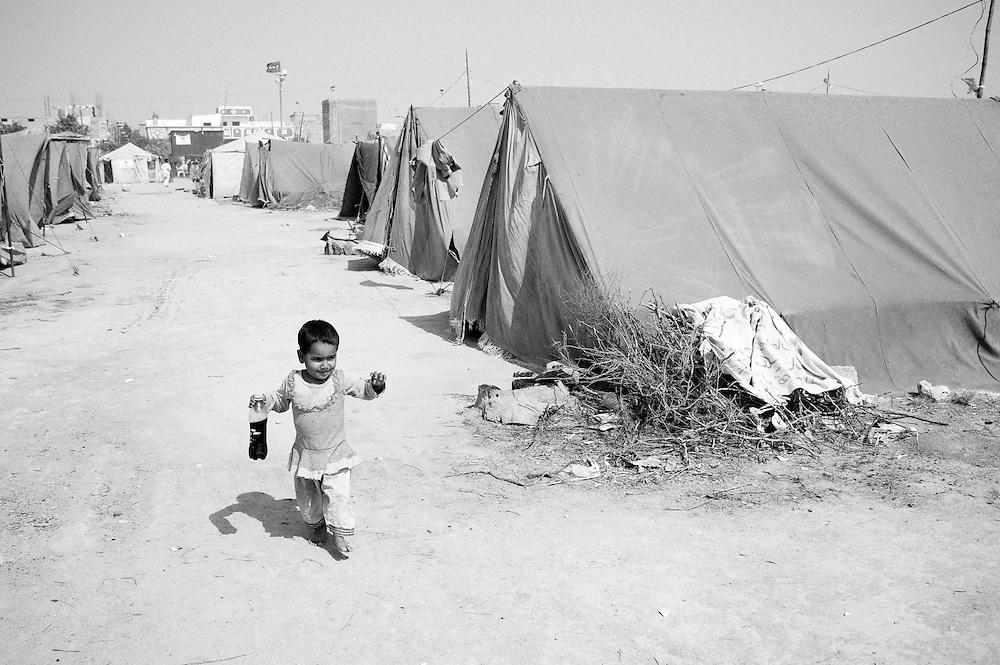 Mehmooda runs in the tent camp with a bottle of local cola her father bought for her. Karachi, Pakistan, 2010