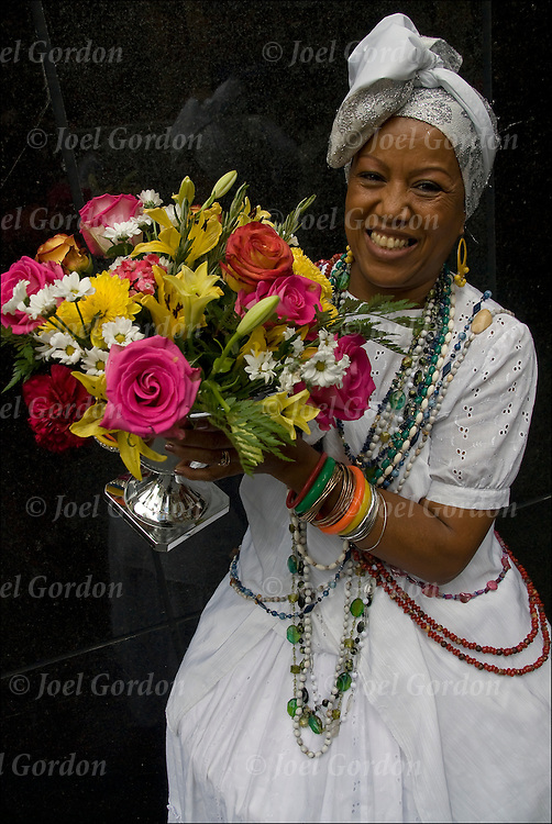 Bahiana American originally from Bahia, Brazil holding vase of flowers.<br /> <br /> Lavagem da Rua 46, the religious blessing purification ritual performed to purity, energize the ground and the Bahianas performers.<br /> <br /> The base elements of water, flowers and perfumes white they dance in traditional, pure white skirts, blouses and headpieces adorned by numerous colorful beads, bracelets, necklaces and rosaries in honor of the the saints, while carrying vases filled with flowers. <br /> <br /> The result of the ritual is the peace, purification and energizing of all people.