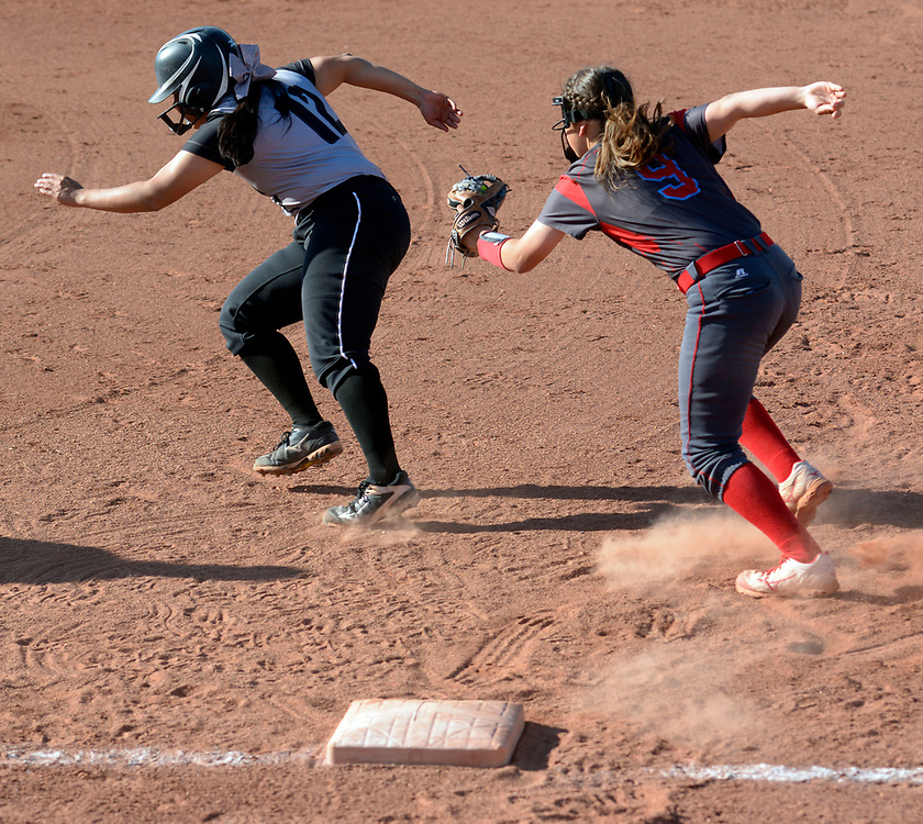 gbs032117l/SPORTS -- Sandia's Jayleen Burton tags out Volcano Vista's Lolly Gallegos, 12, catching her off first base during the game at Volcano Vista on Tuesday, March 21, 2017. (Greg Sorber/Albuquerque Journal)