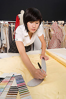 Female dressmaker measuring fabric
