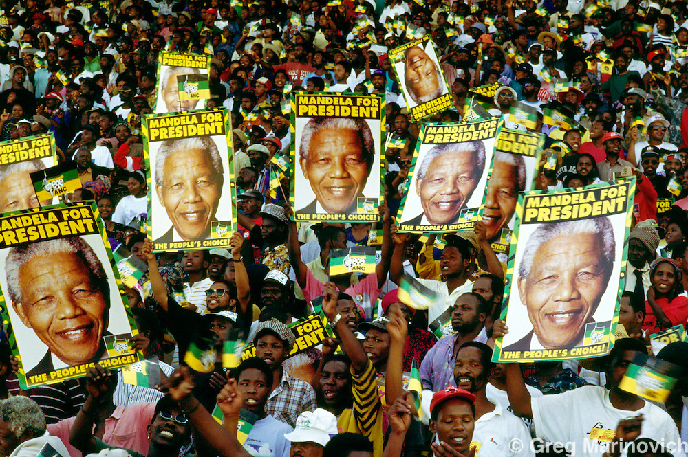 ANC supporters hold up posters with the face of Nelson Mandela during a Campaign Rally ahead of South Africa's first non racial elections. 1994.