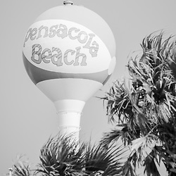 Pensacola Beach water tower beach ball and plam trees black and white photo. Pensacola Beach is a coastal city on Santa Rosa Island in the Emerald Coast of the Southeastern United States of America. Photo is vertical and high resolution. Copyright ⓒ 2018 Paul Velgos with All Rights Reserved.