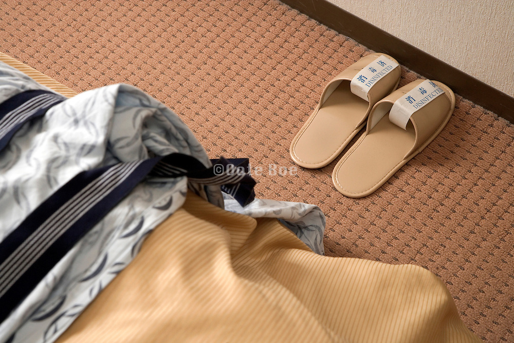 unused slippers at the end of bed in a Japanese hotel