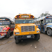 Three chicken buses behind the Mercado Municipal (town market) in Antigua, Guatemala. From this extensive central bus interchange the routes radiate out across Guatemala. Often brightly painted, the chicken buses are retrofitted American school buses and provide a cheap mode of transport throughout the country.