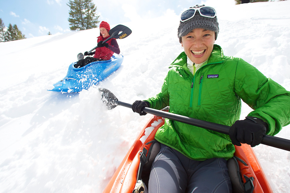 Two girls using kayaks for a wintertime ride down a snow covered slope in Sun Valley Idaho