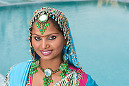 Portrait of a beautiful young Indian woman in a turquoise blue sari and headdress.