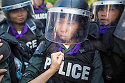 22 DECEMBER 2013 - BANGKOK, THAILAND: A protestor tries to push a Thai riot police officer out of the way at a roadblock preventing access to the home of caretaker Prime Minister Yingluck Shinawatra. Hundreds of thousands of Thais gathered in Bangkok Sunday in a series of protests against the caretaker government of Yingluck Shinawatra. The protests are a continuation of protests that started in early November and have caused the dissolution of the Pheu Thai led government of Yingluck Shinawatra. Protestors congregated at home of Yingluck and launched a series of motorcades that effectively gridlocked the city. Yingluck was not home when protestors picketed her home.     PHOTO BY JACK KURTZ