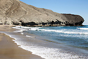 Rocky headland at Playa Monsul sandy beach, Cabo de Gata natural park, Almeria, Spain