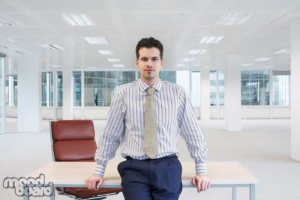 Office worker perching on edge of table in empty office space