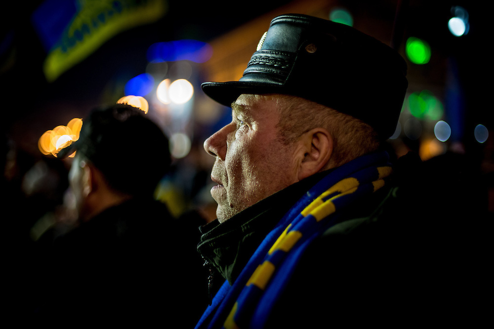 A man looks at the stage and listens to the speeches, on the Independance Square, at night.