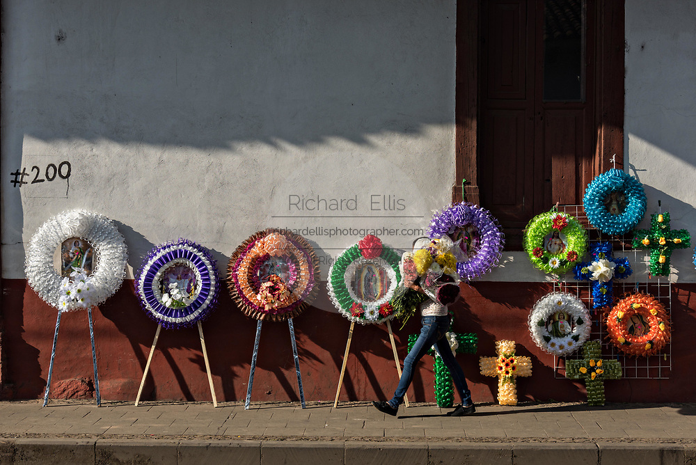 A young girl carries flowers past colorful memorial wreaths on sale for the Day of the Dead festival along a street in Santa Clara del Cobre, Michoacan, Mexico.