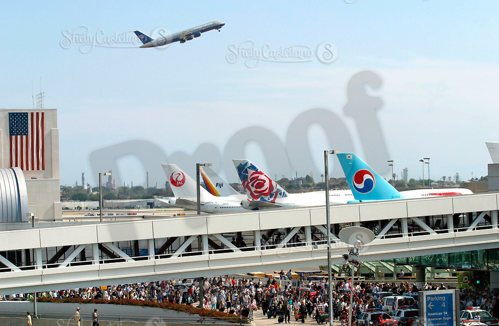 Dec 09, 2002; Los Angeles, CA, USA; File Photo: Jul 04, 2002. Domestic United Airlines plane takes off over grounded international planes on the tarmac waiting for thousands of passengers to board at Los Angeles International airport. United Airlines has filed bankruptcy, the largest filing in aviation history. The airline giant is losing an estimated $8 million a day and is due to pay $1 billion debt this week which forced them to file for federal bankruptcy court protection after losing an estimated $4 billion in the last two years. United operates 1,700 flights a day, about 20 percent of all US flights.<br />