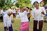 28 JUNE 2014 - DAN SAI, LOEI, THAILAND: Women dance at Wat Ponchai in Dan Sai during the Ghost Festival. Phi Ta Khon (also spelled Pee Ta Khon) is the Ghost Festival. Over three days, the town's residents invite protection from Phra U-pakut, the spirit that lives in the Mun River, which runs through Dan Sai. People in the town and surrounding villages wear costumes made of patchwork and ornate masks and are thought be ghosts who were awoken from the dead when Vessantra Jataka (one of the Buddhas) came out of the forest.    PHOTO BY JACK KURTZ