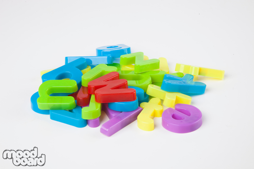 Pile of colorful alphabet magnets over white background