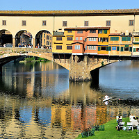 Ponte Vecchio East Side and Arno River in Florence, Italy<br /> Begin exploring Florence early in the morning before the tourists arrive. The scenery is magical as evident by this scene from Lungarno degli Archibugieri (north riverbank). Watch a rower glide along the Arno. Overlook an art class painting Ponte Vecchio. This 105 foot, stone arch span was constructed in 1218 and rebuilt in 1345. This bridge is the only one to survive World War II and the devastating flood of 1966. Wow, this Florence icon is gorgeous!