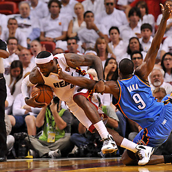 Jun 17, 2012; Miam, FL, USA; Miami Heat small forward LeBron James (6) and Oklahoma City Thunder power forward Serge Ibaka (9) get tied up during the third quarter in game three in the 2012 NBA Finals at the American Airlines Arena. Mandatory Credit: Derick E. Hingle-US PRESSWIRE