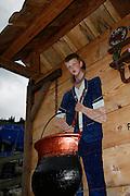 Junger Bub schaut durch ein Guckloch mit Käsekessi, Schaukäserei Moléson Village, Greyerz, Freiburg. Garçon guigne à travers un judas pour se faire photographier, Moléson Village, juillet 2009.