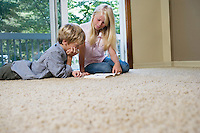Brother and sister (5-9) reading book on carpet