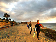 Two young surfers carrying surfboards heading down to the beach at Del Mar, CA at sunset.
